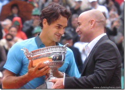 2009 french open - andre agassi hands roger federer the cup