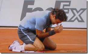 2009 french open - federer collapses in front of 'Fed Ex' sign after winning the french open